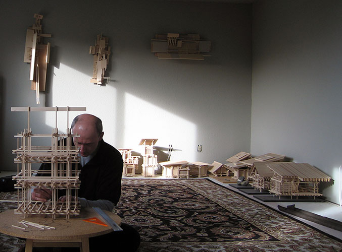 The artist Maciek Jozefowicz working on one of his architectural model sculptures